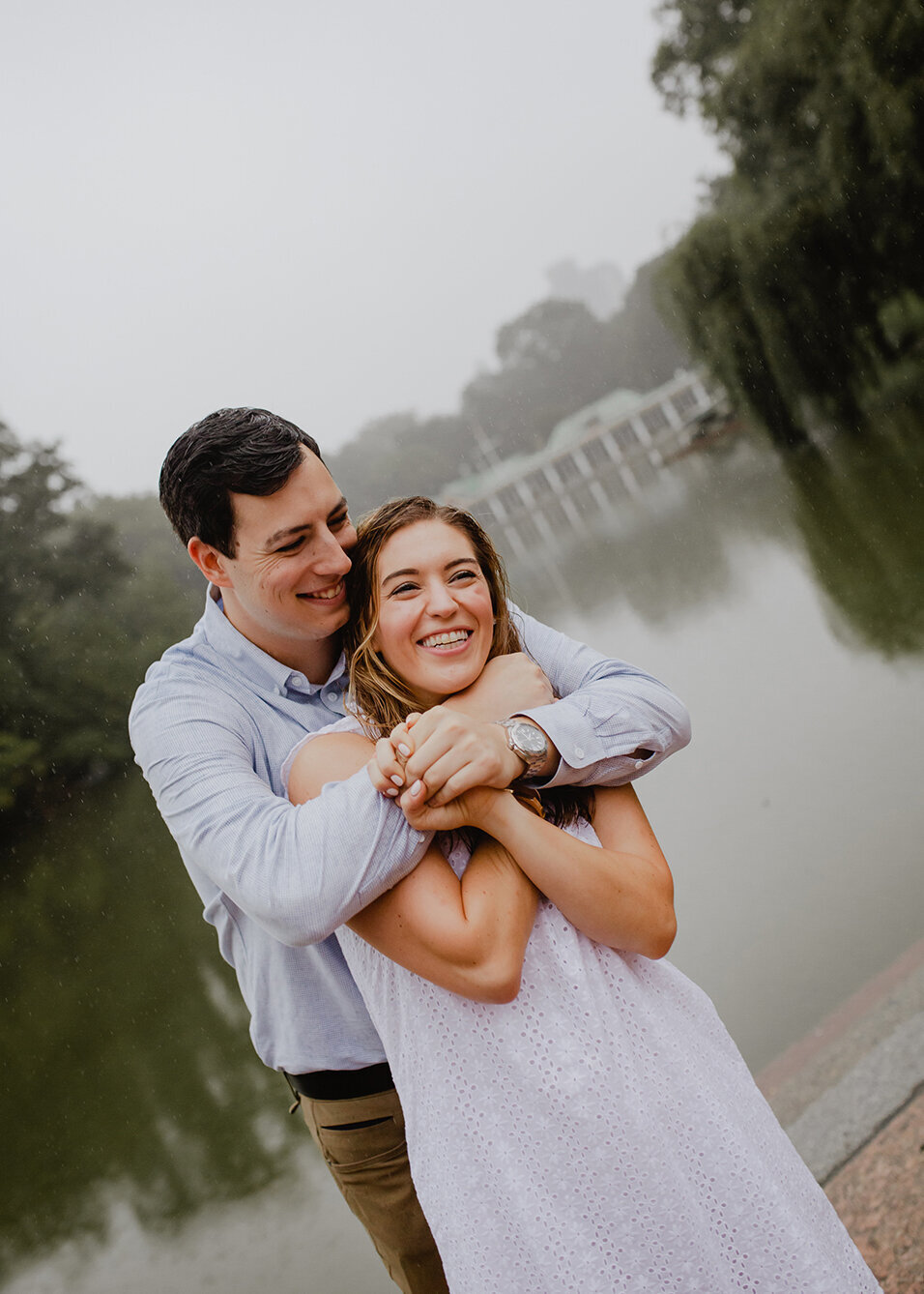 A newly engaged couple celebrates in front of the Boathouse in Central Park, New York. The man wraps his arms around his bride-to-be.