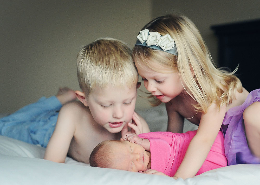 big brother and big sister admiring baby sister