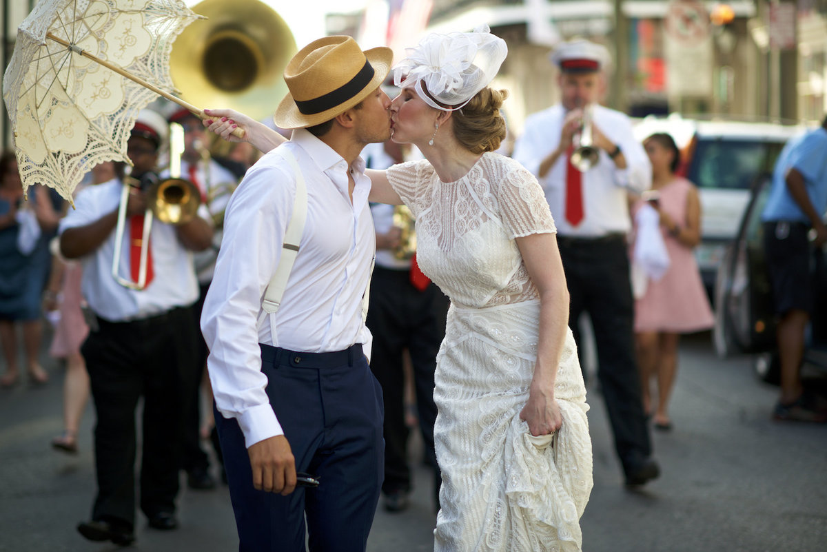 a wedding couple kisses during a second line parade at their wedding in New Orleans