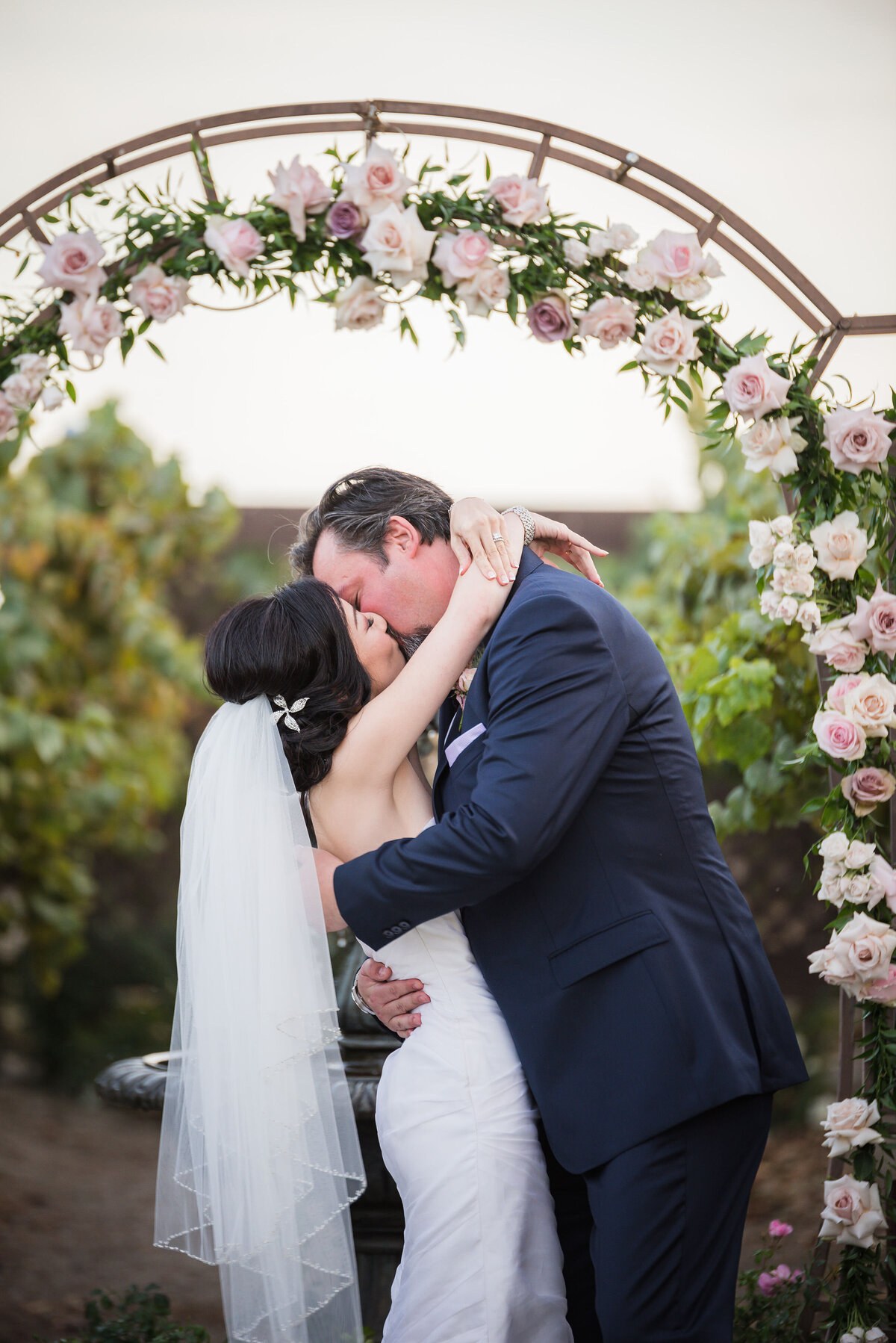 pink rose arch with bride and groom
