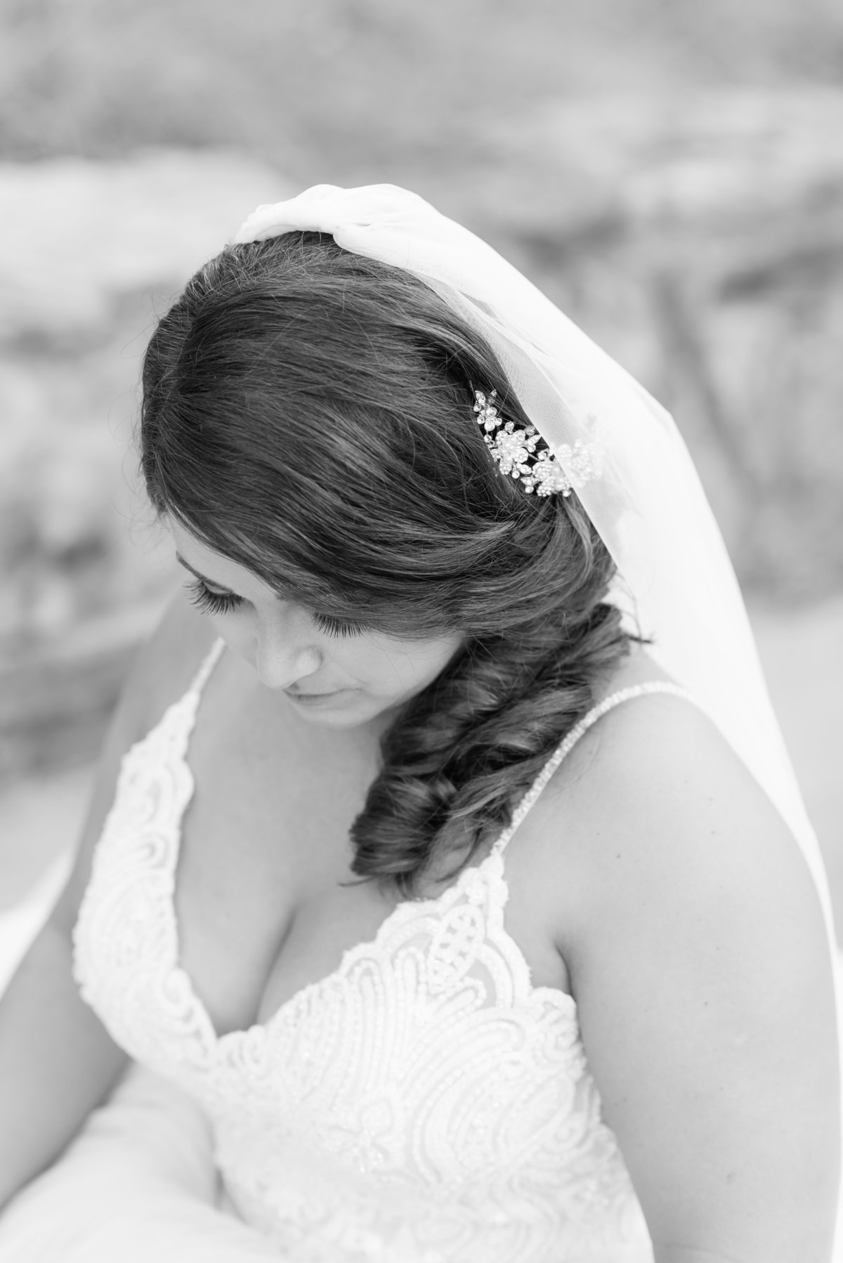 a black and white photograph of a bride sitting on a brick bridge on a golf course with the focus on her side hair do and jeweled hair piece at Sedgefield Country Club, Greensboro NC
