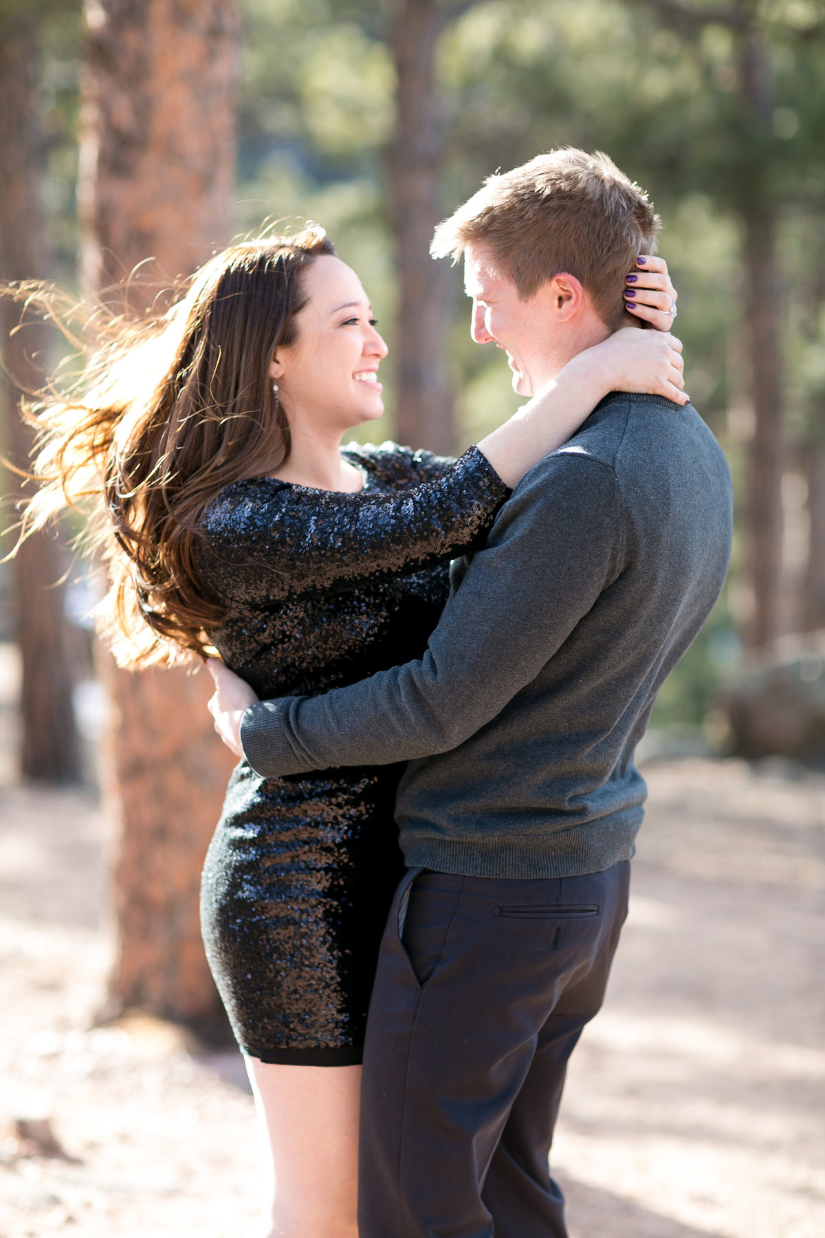 Couple smiling at each other during their Colorado engagement photos. Girl in black sequin dress