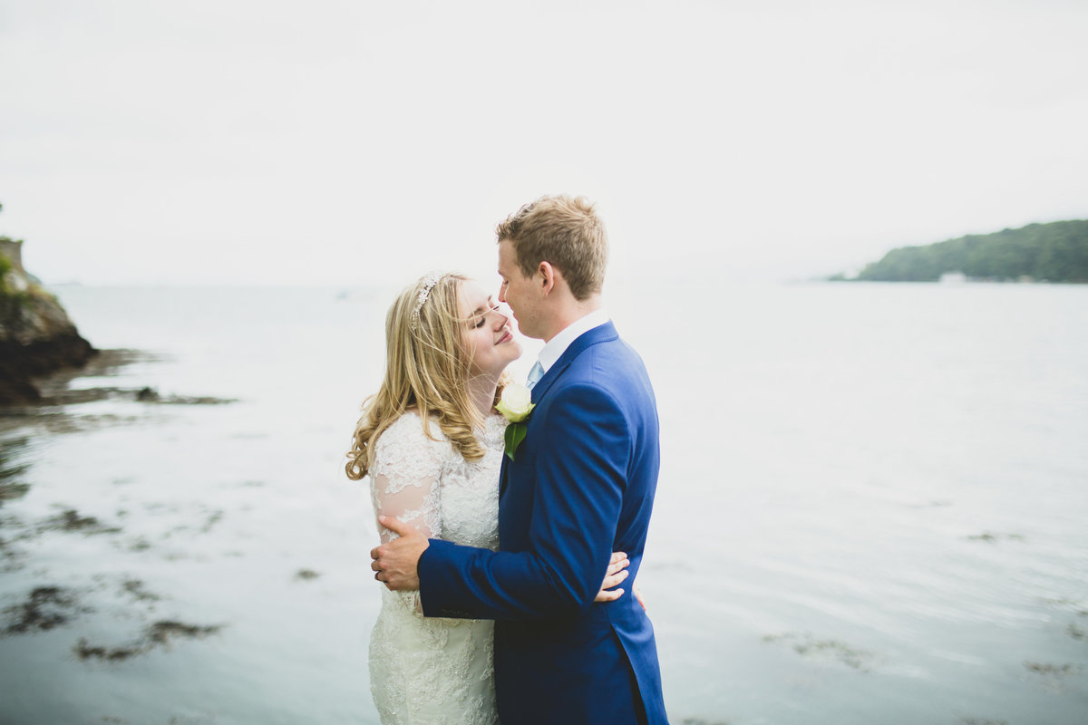 bride and groom kissing in front of the sea