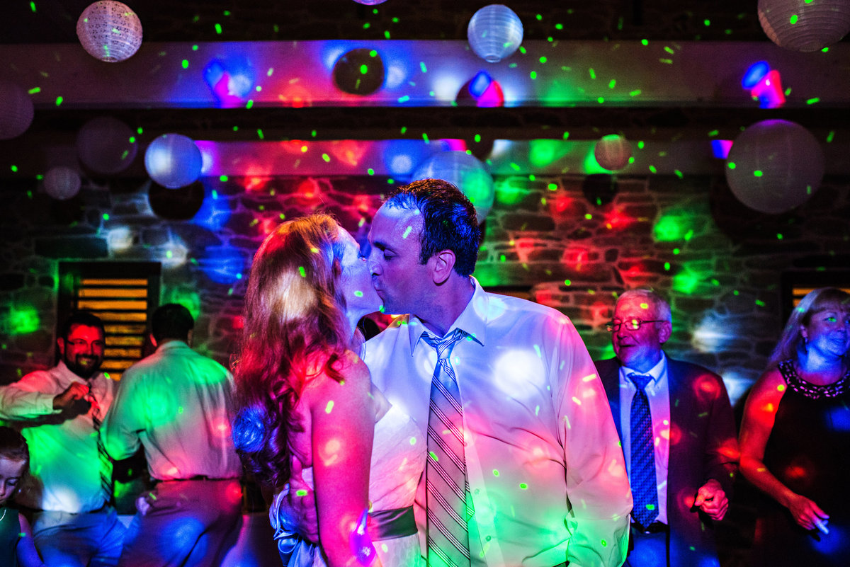 A newly married couple make out on the dance floor of their reception at Pheasant Run Farm in Lancaster, PA.