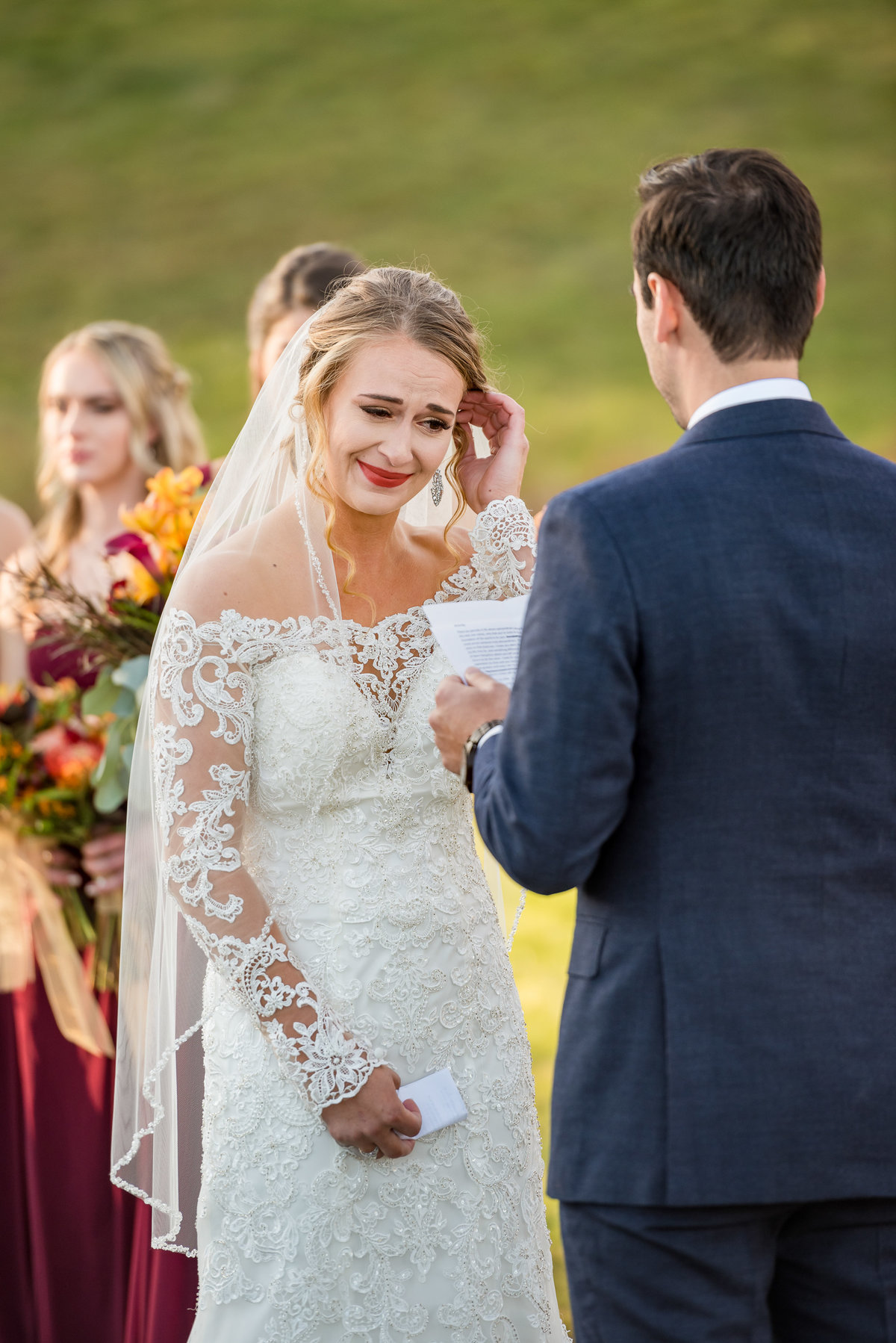 bride crying and wiping away tear during ceremony