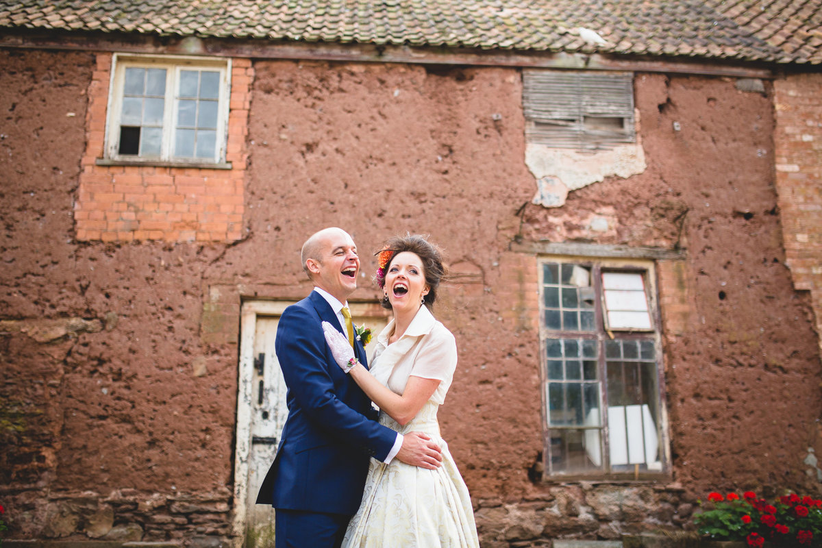 couple in front of a old barn at maunsel house laughing