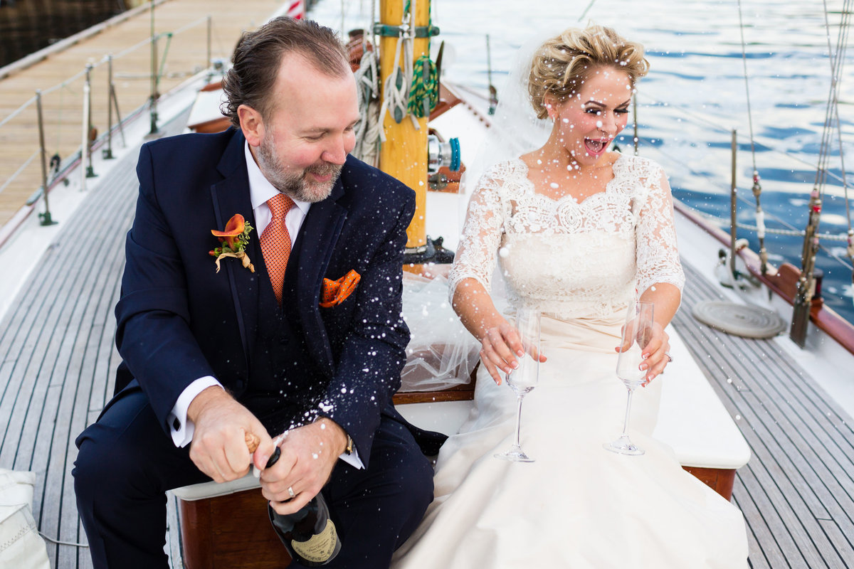 Maine Elopement Photographer Silverlinings Sailing the bride and groom have a toast after their wedding ceremony out on the Atlantic Ocean on a sailboat