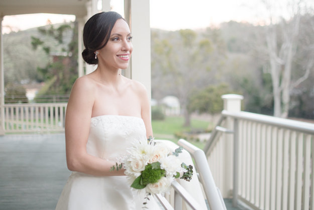 Bride with brown eyes and brown hair in updo white florals on a porch with classic bridal makeup for hazel eyes