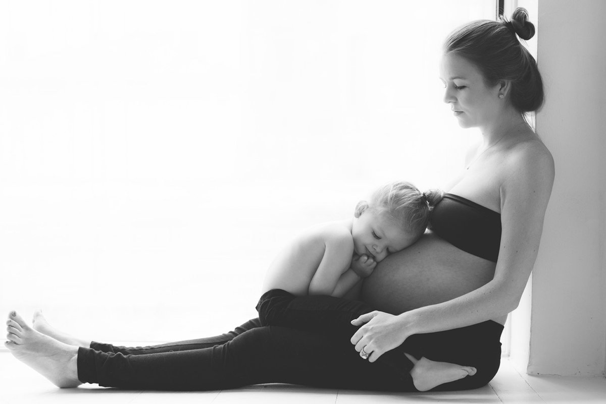 a toddler girl snuggles the belly of her pregnant mother