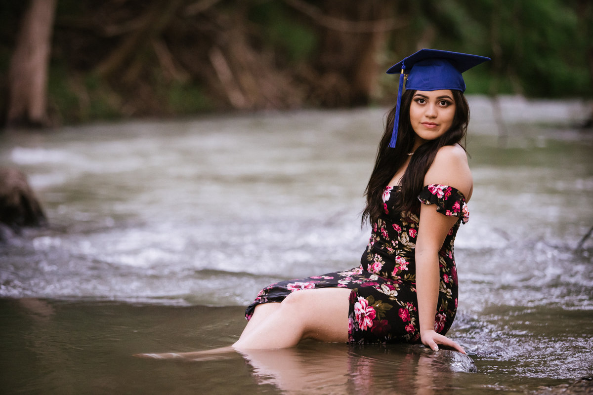senior girl in high school cap and dress sitting in river water by San Antonio senior photographer