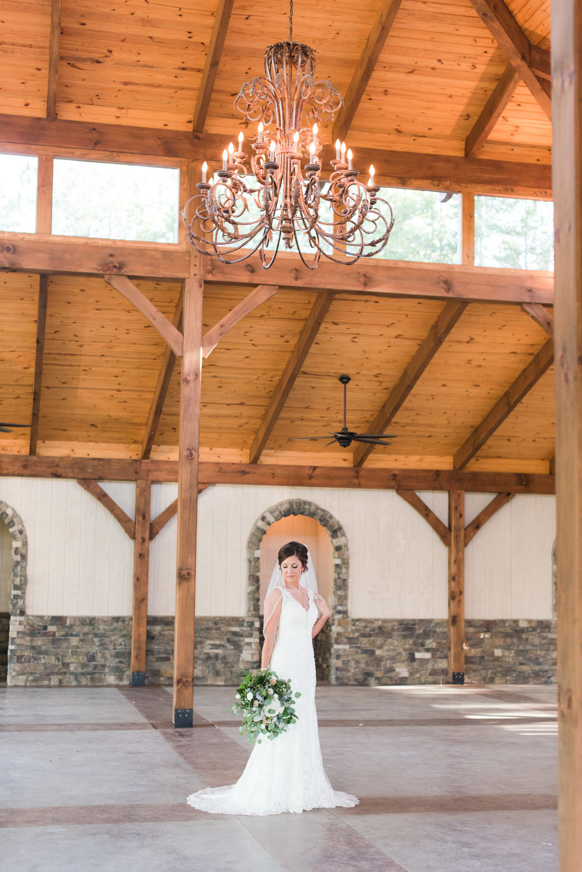 a bride wearing a laced thin strapped wedding dress holding a lush green and white wedding bouquet standing underneath a grand chandelier at Meadows at Walnut Cove