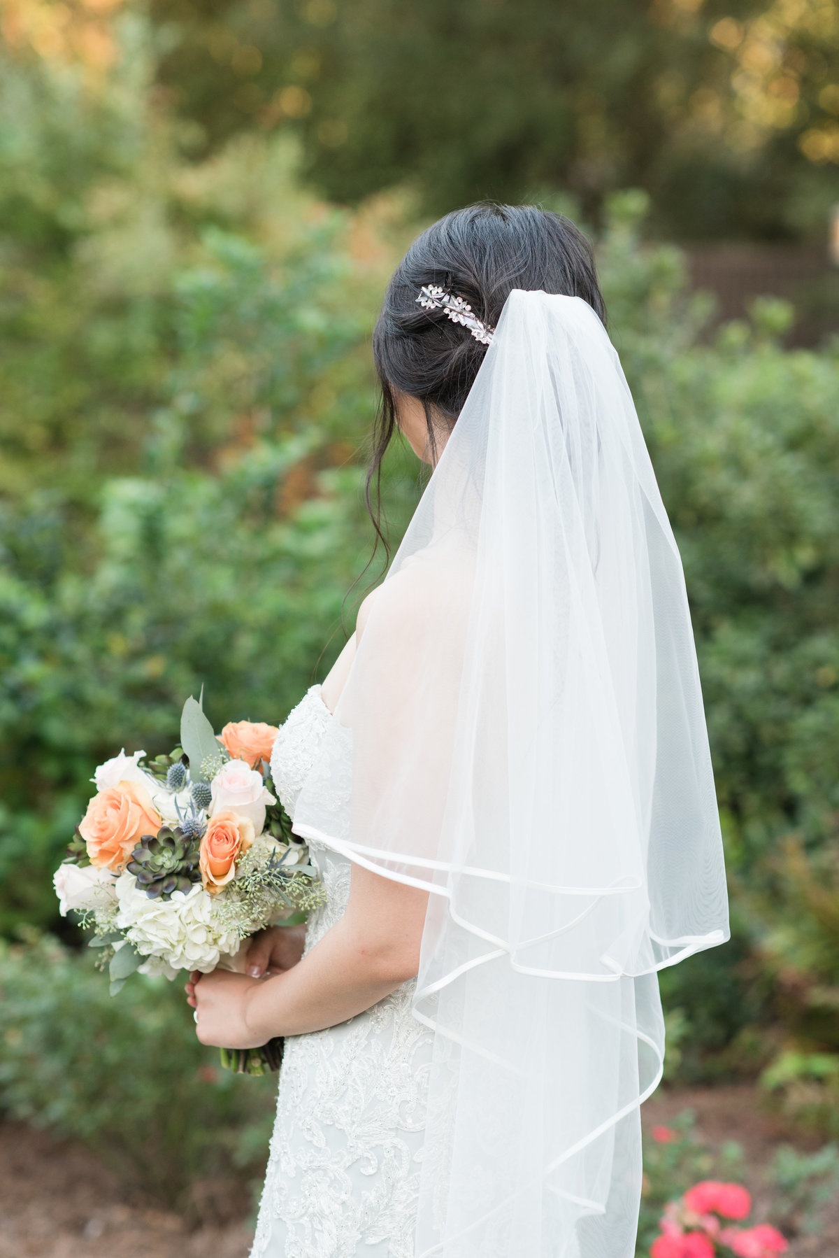 a bride wearing a strapless light blue wedding dress with mid-length veil holding white and orange wedding bouquet in front of an elegant little garden at Barclay Villa