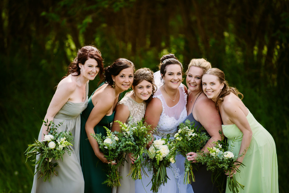 Bridesmaids at the gorgeous Dunvegan Garden in Fort McMurray Alberta.  I am so in love with their mismatched green dresses and the neutral tones of the bouquets made by The Personal Florist, also located in Fort McMurray.