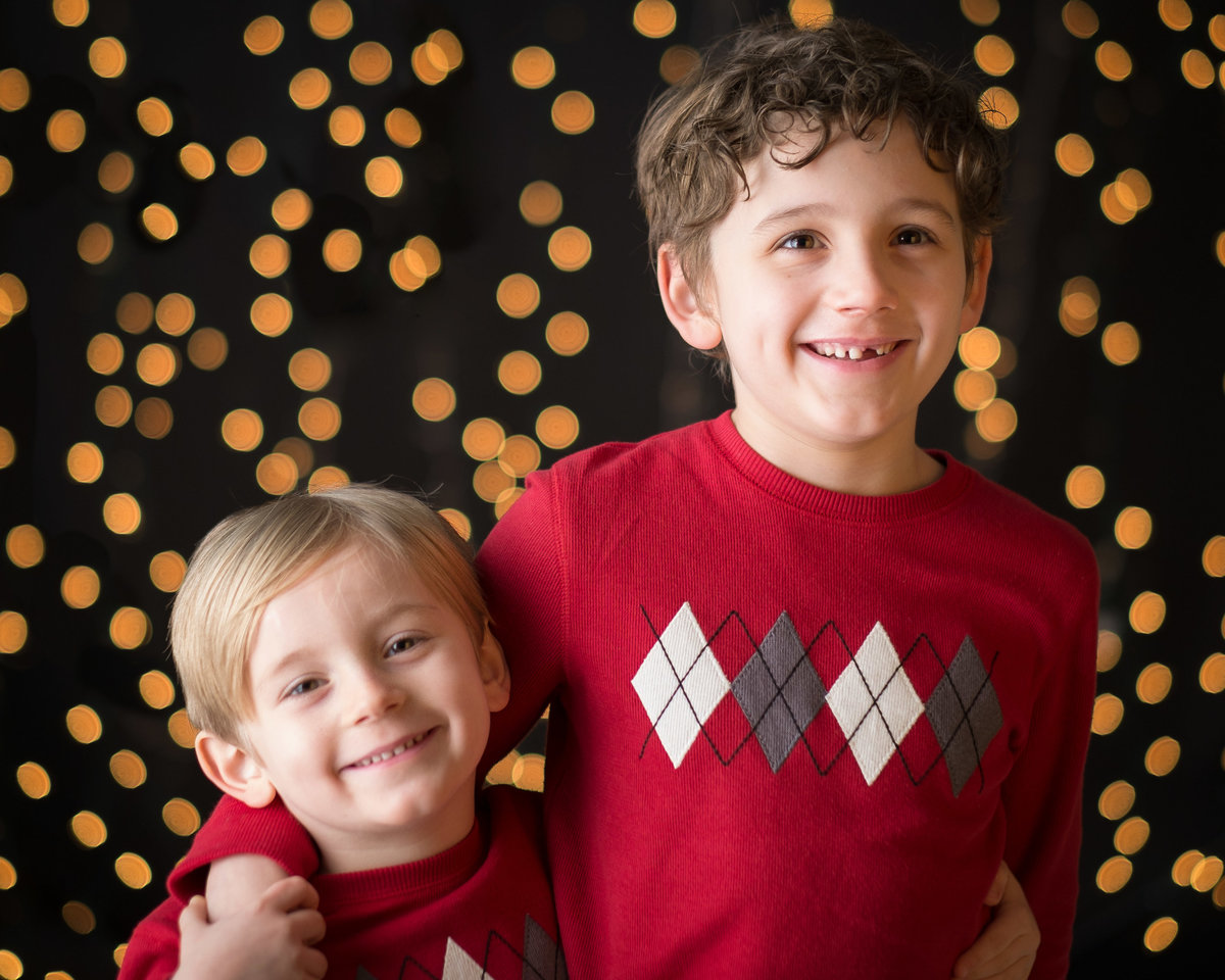 Brothers pose for Christmas portrait with light strings, Chicago.