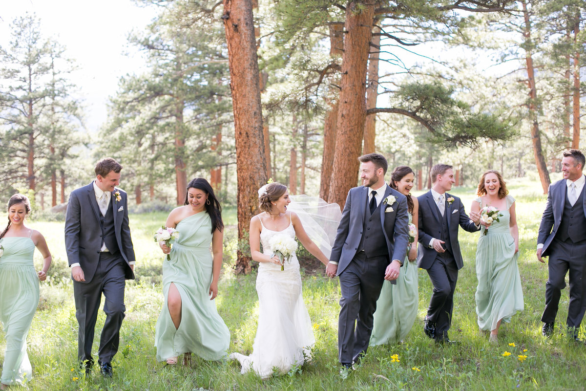 Bridal party walking through a field at Della Terra