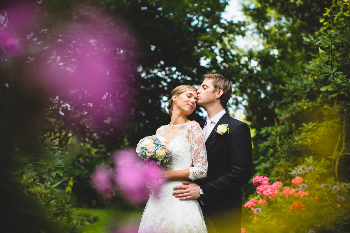 Bride kissing groom in a gardens with pink flowers