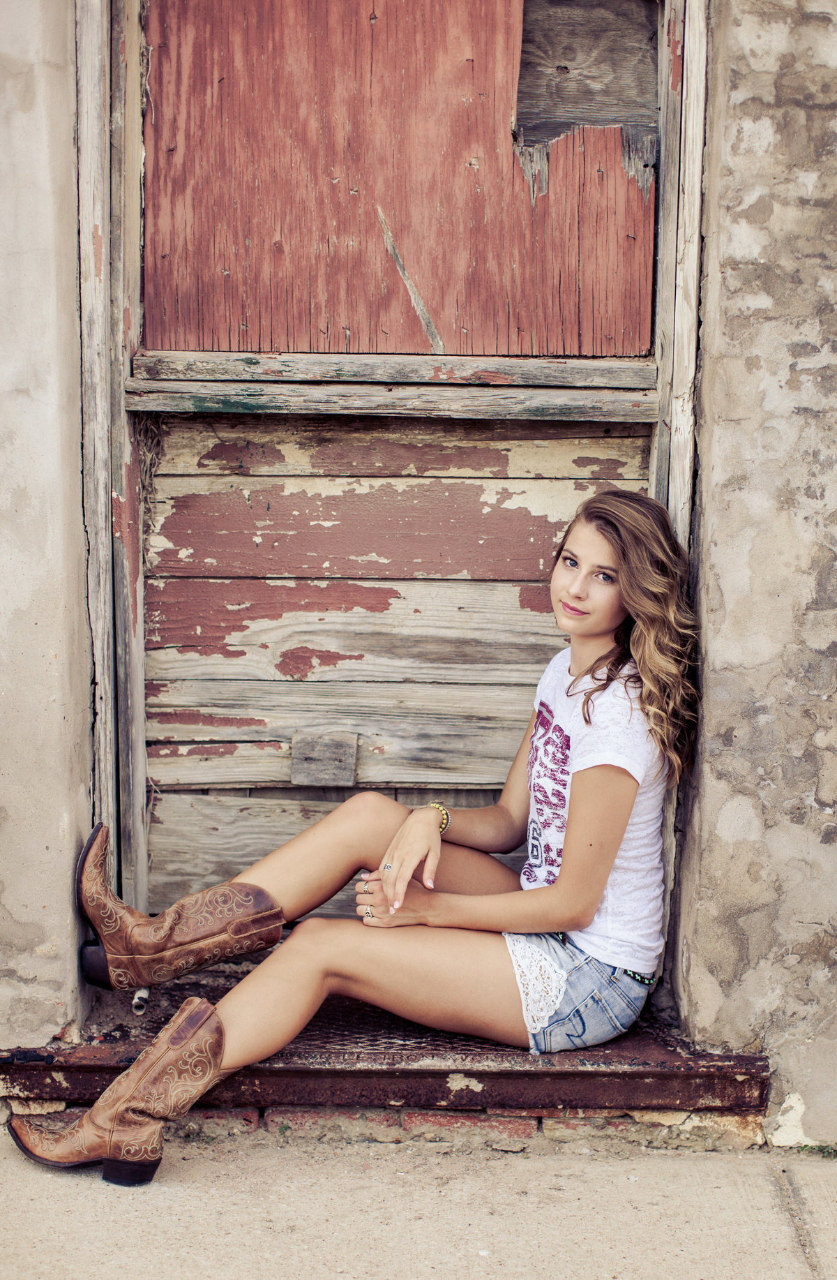 Girl in rustic doorway in cowboy boots