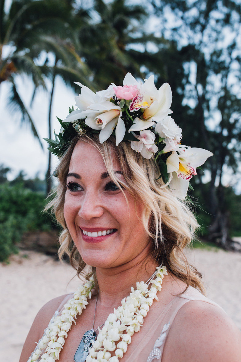 Bride with haku lei and pikake lei smiling after she elopes on the North Shore