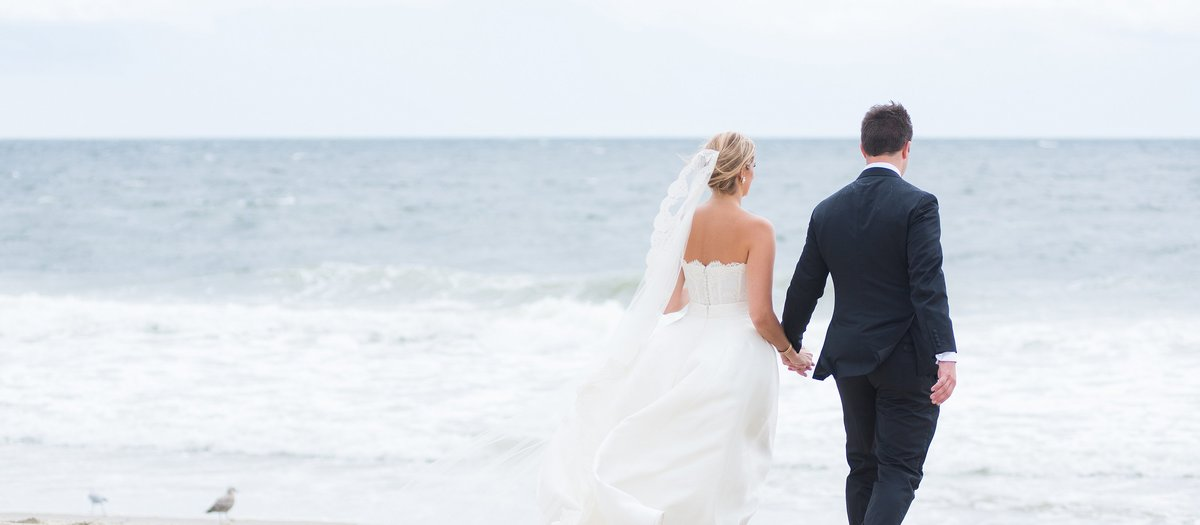 Bride and Groom walking on the Beach on a Windy Day at Spring Lake Bath and Tennis Club in Spring Lake, New Jersey Photo