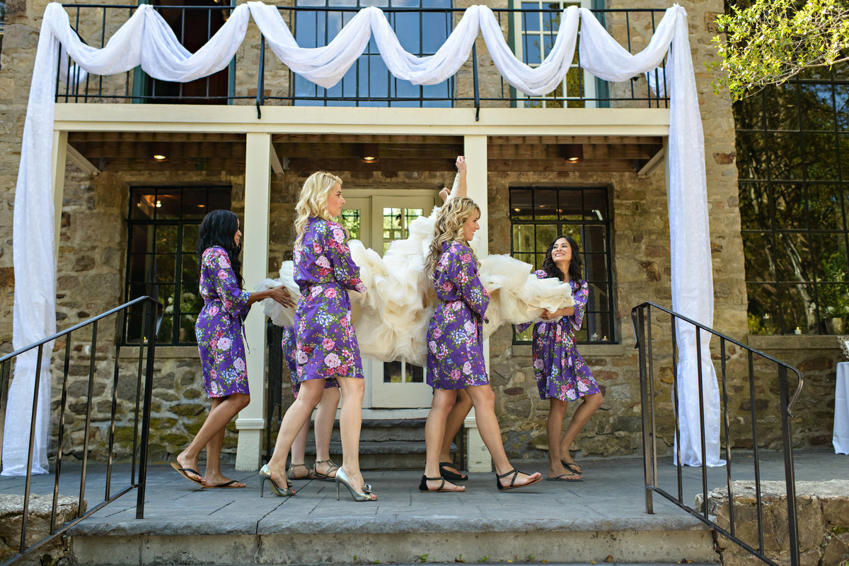 Bridesmaids carry the bride's wedding dress to the bridal suite at the Holly Hedge Estate Wedding.