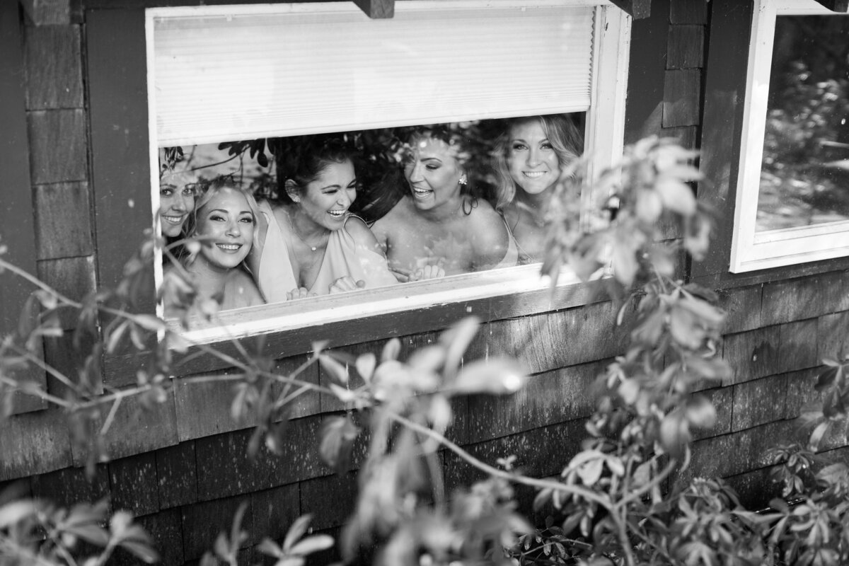 bridesmaids peaking trough a window