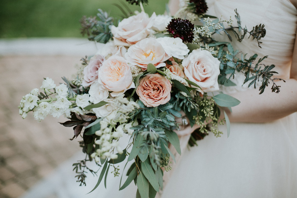 Bride holds purple blush and white bouquet by Meg Catherine Florals