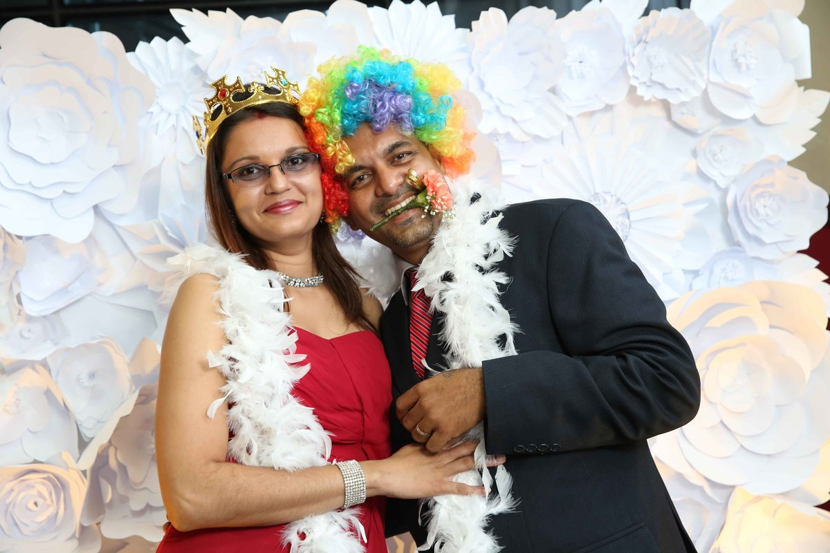 Man and woman pose with fun wigs and head gear in front of 3d background. Photobooth by Ross Photography, Trinidad, W.I..
