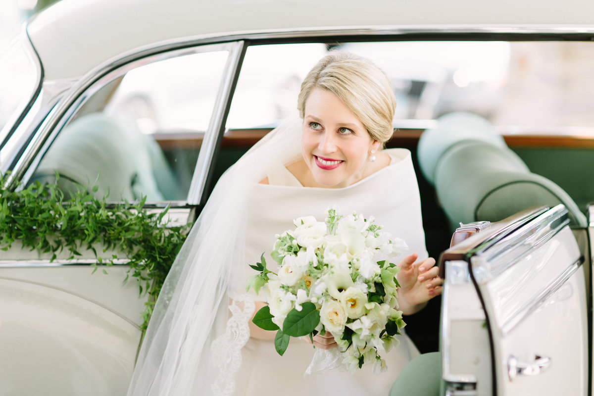 bride exiting vintage car with cascading bouquet
