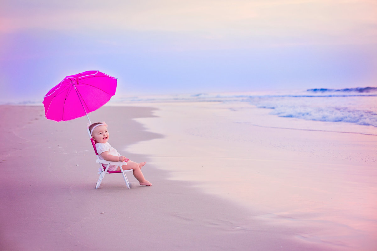 charlotte family photographer jamie lucido creates gorgeous image of child sitting on a chair with an umbrella at Outer Banks, north carolina shore