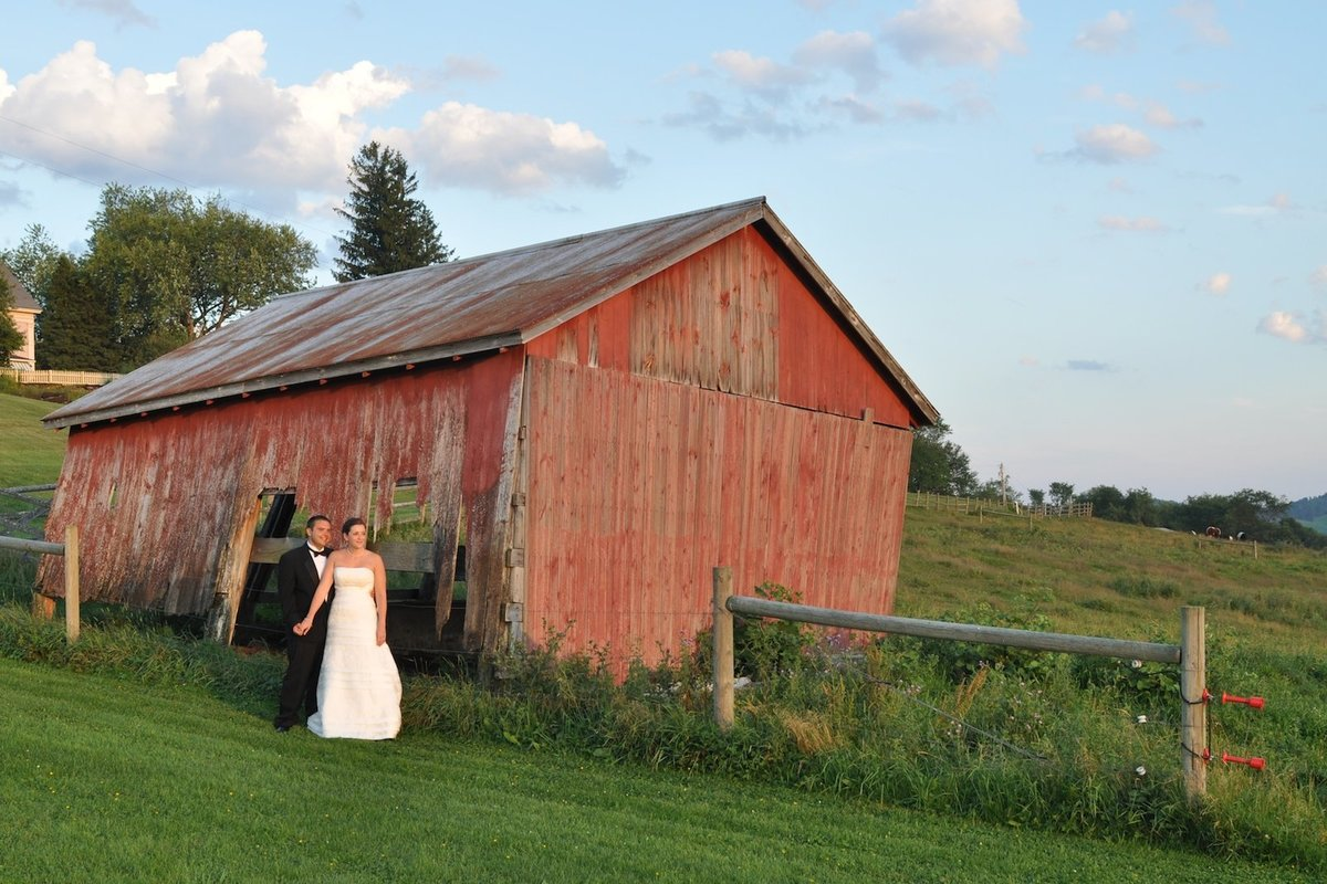 bride and groom in a relaxed wedding photo in front of a red barn
