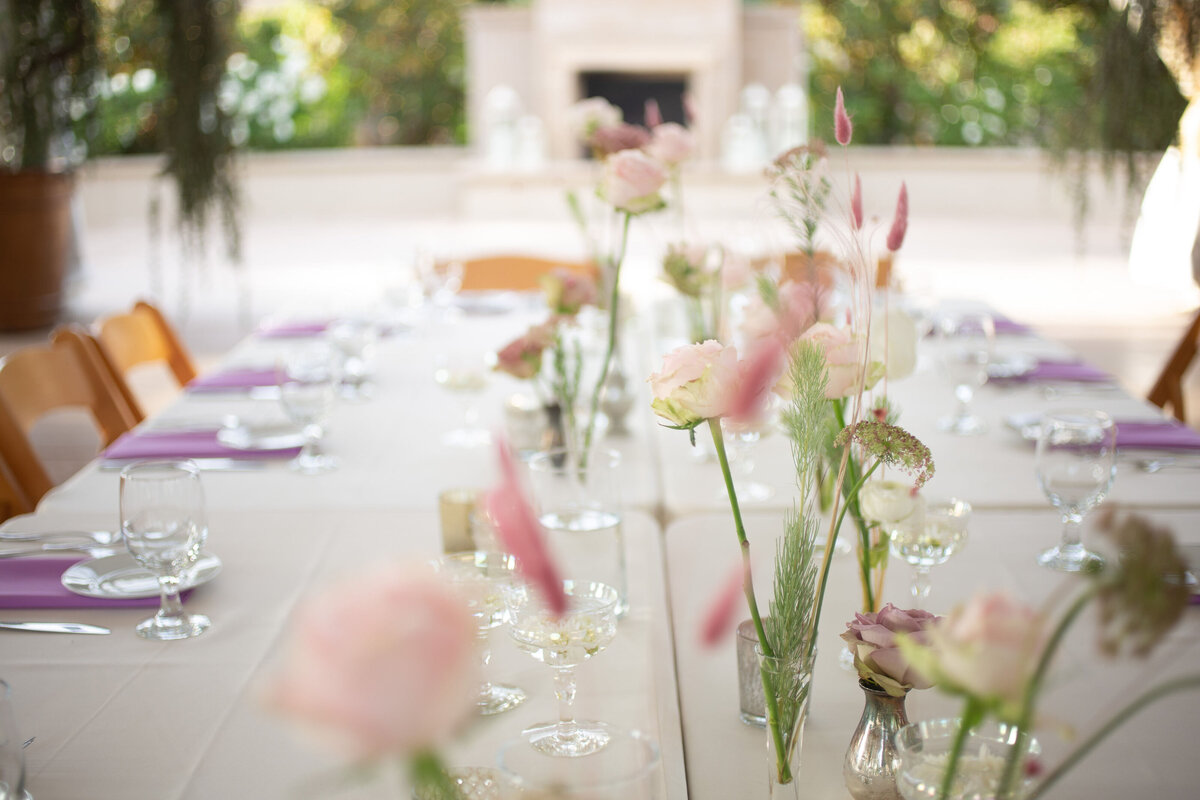 long head table decorated with bunny tail and pink roses