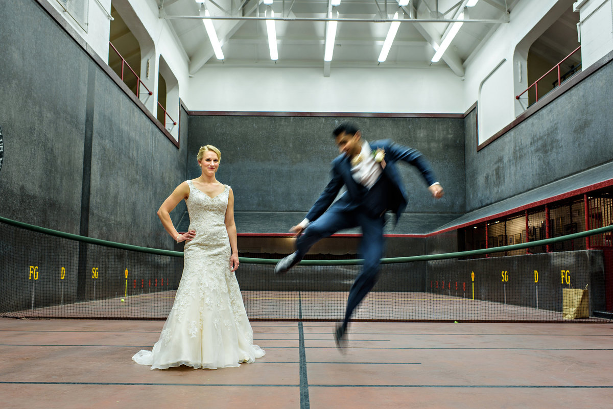 A bride watches her groom jump through the air on the tennis court in Philadelphia before the wedding.