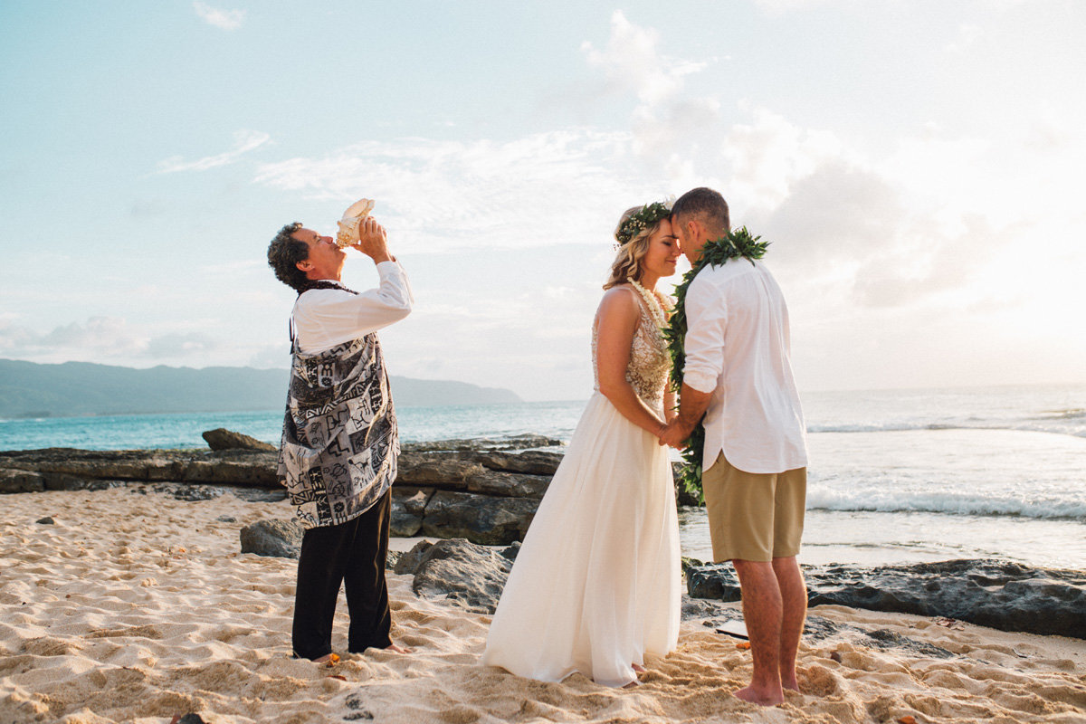 Bride and groom exchanging  ha during Hawaiian wedding tradition