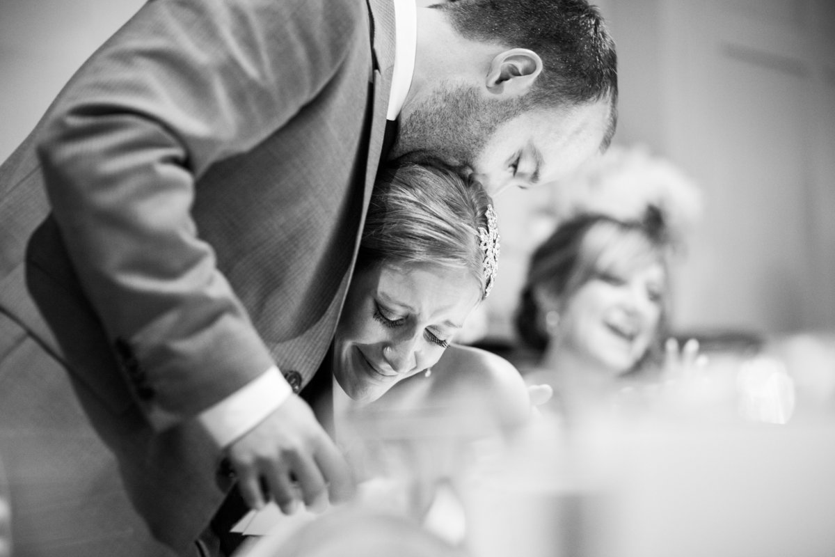 bride and groom embrace during an emotional wedding speech