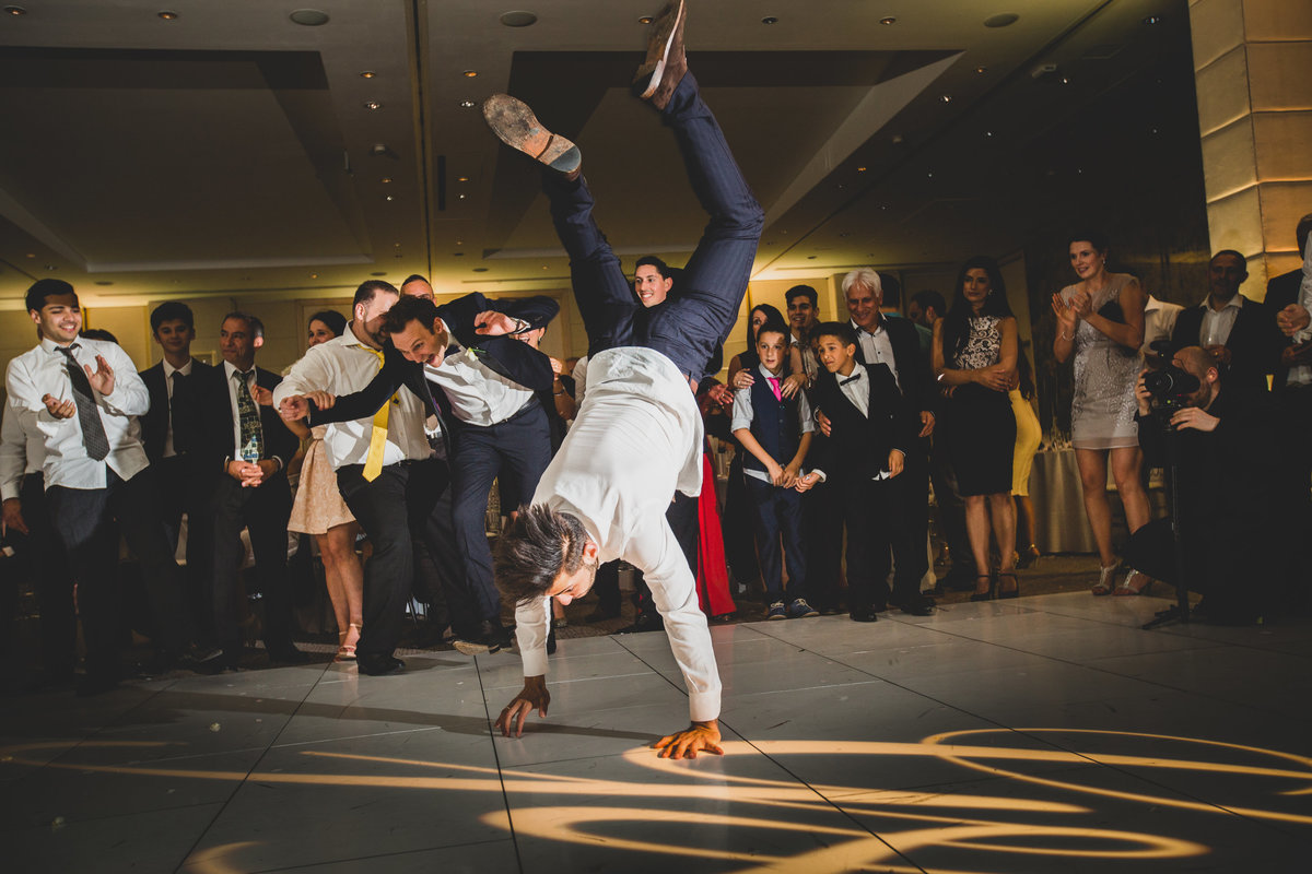 a wedding guest doing a handstand on the dancefloor at greek wedding in the grove hotel