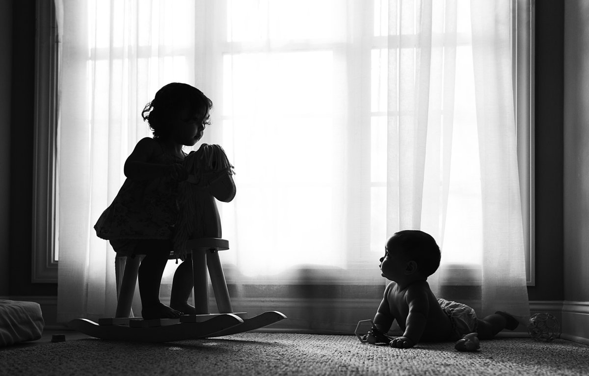 charlotte documentary photographer jamie lucido captures a beautiful silhouette of children at play in a playroom next to a large window