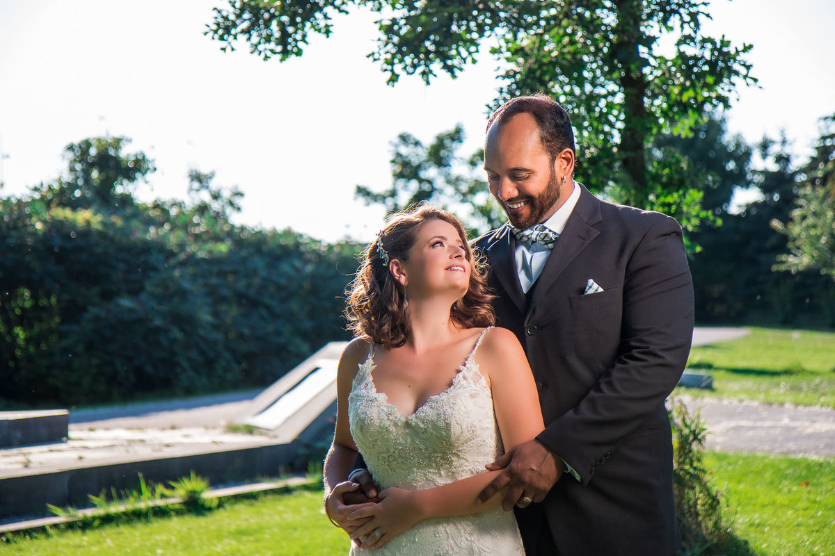 Groom looks down at his bride while she looks up at him while he holds her from behind as they smile at each other at the Toronto Lakeshore Waterfront