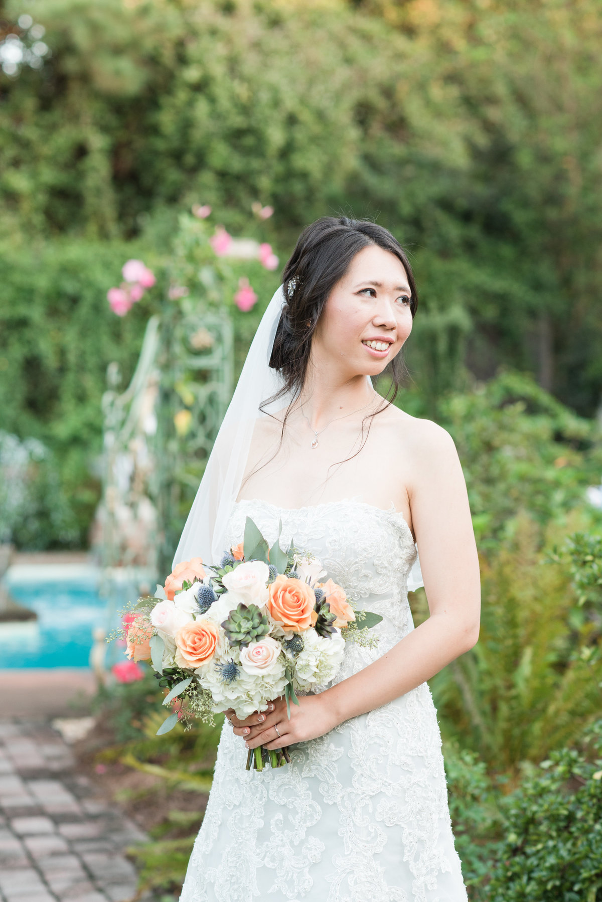 a bride wearing a strapless light blue wedding dress with mid-length veil holding white and orange wedding bouquet in front of an elegant little garden with pond looking off with a smile on her face at Barclay Villa