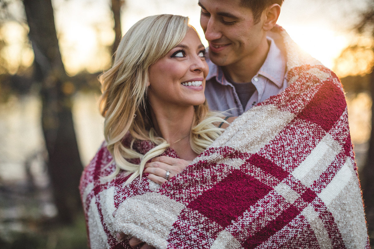 couple keeping warm under a blanket during their engagement photography session