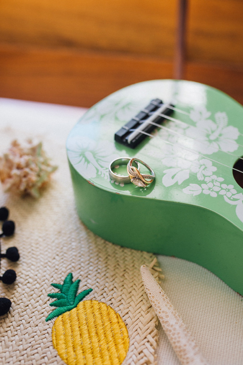 Wedding rings on a green ukelele by a straw hat with a pineapple