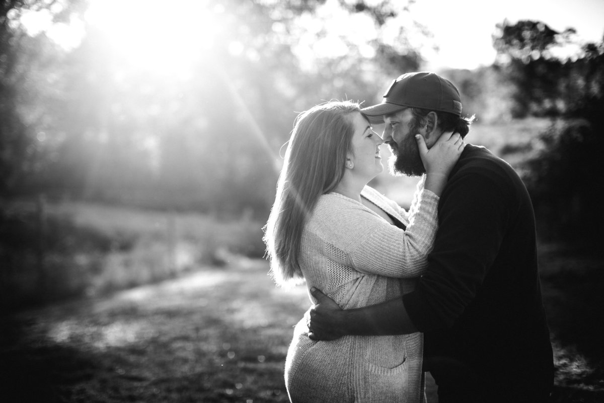 Black and white her hands on his cheeks with sun flare in the background engagement photo by Knoxville Wedding Photographer, Amanda May Photos.