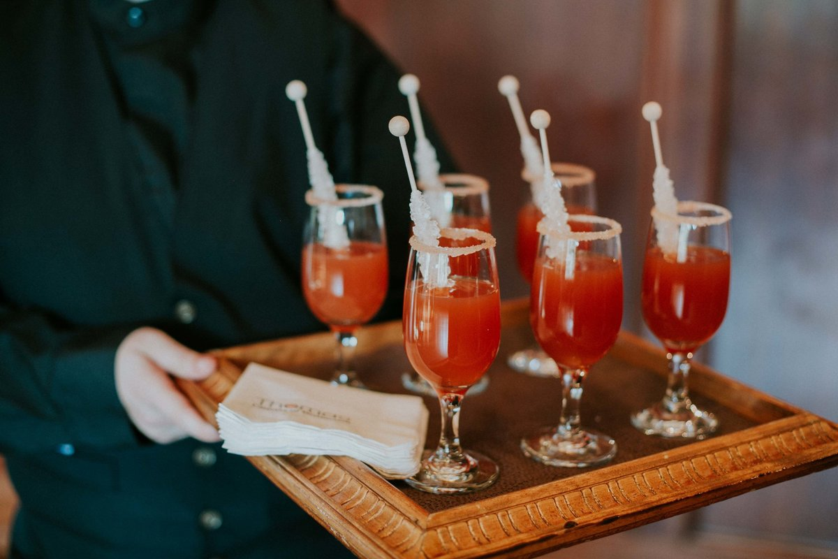Thomas Catering Caterer holds a glass of special drinks with rock candy at Laurel Hall wedding