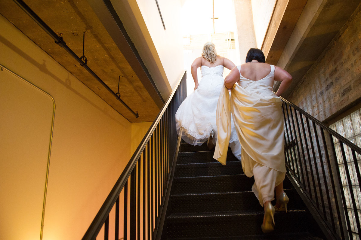 Two brides ascend stairs after wedding ceremony, Chicago IL.