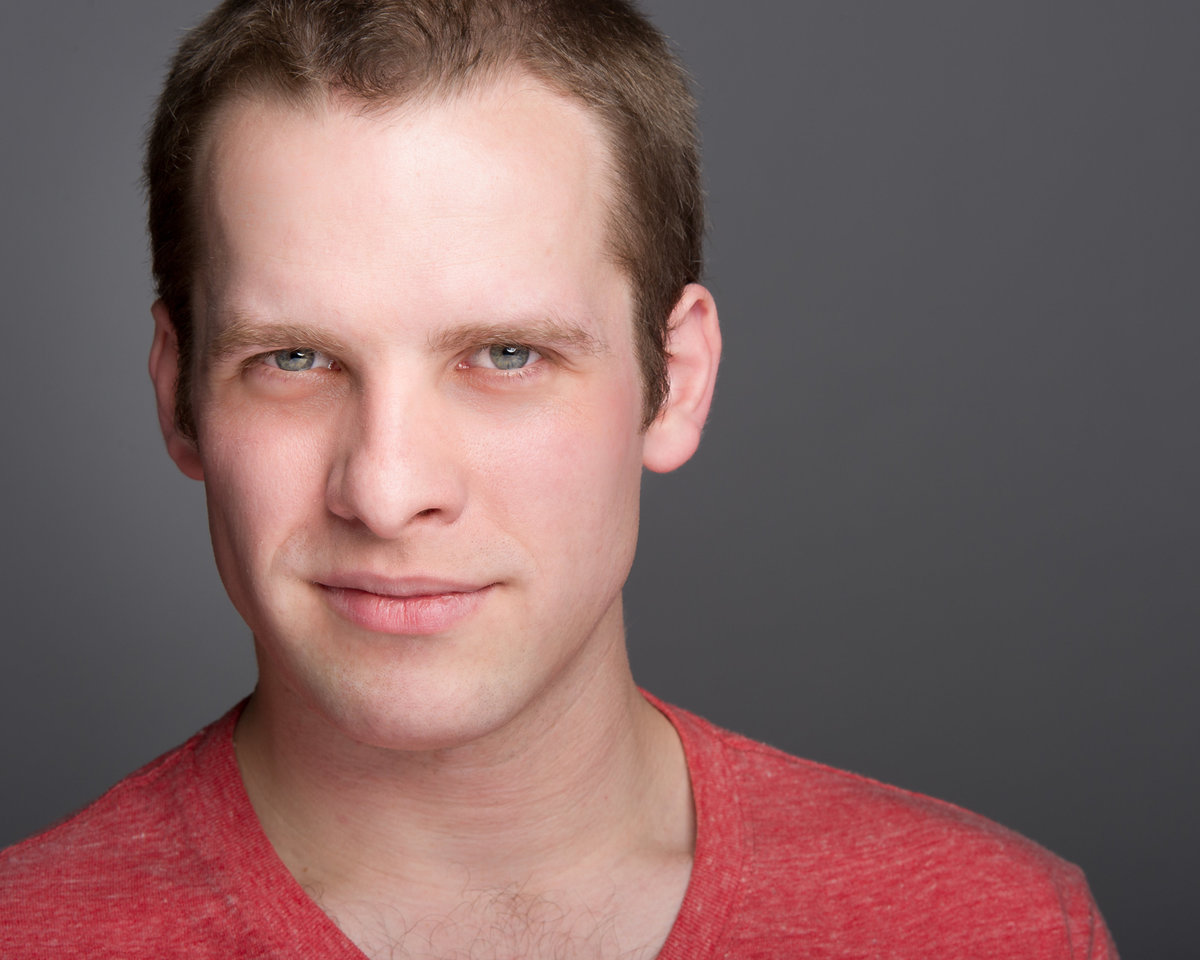 Chicago actor, male, grey background, short hair.
