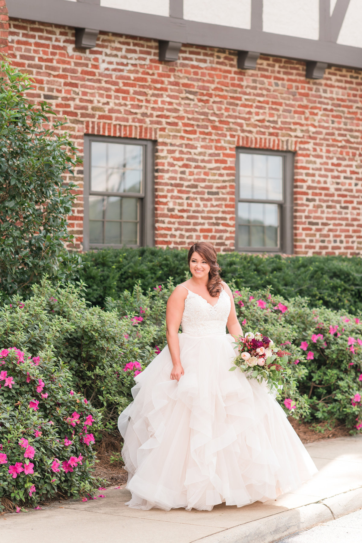 bride wearing a champagne wedding dress standing in front of a brick building holding a pink and red roses wedding bouquet at Sedgefield Country Club, Greensboro NC