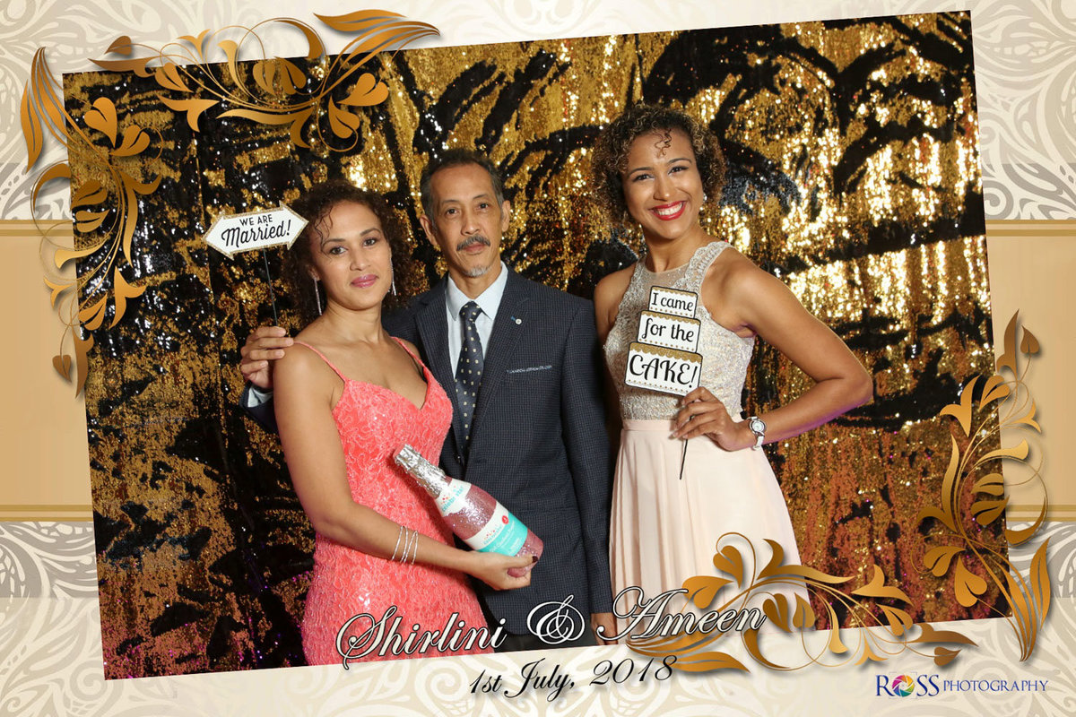 Man and two women hold signs in photobooth. Photobooth by Ross Photography, Trinidad, W.I..