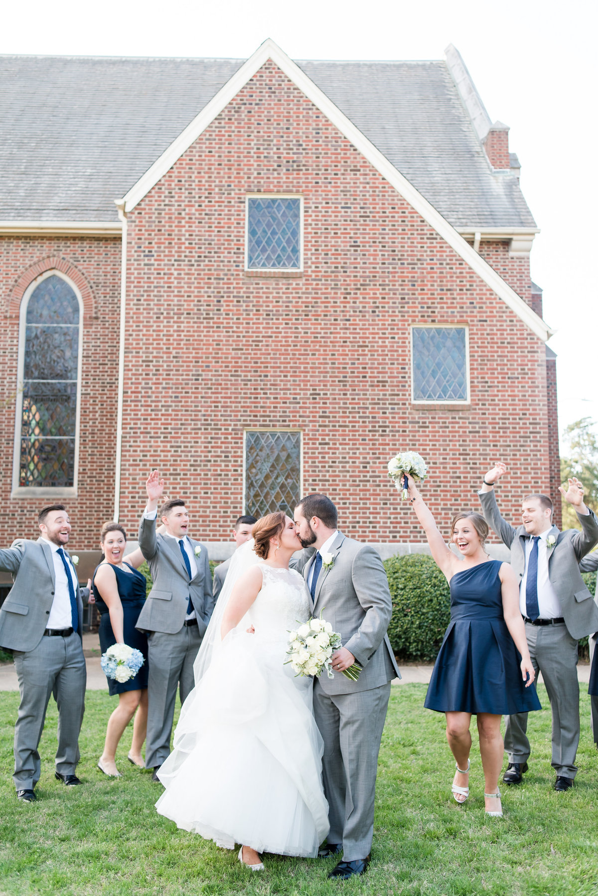 a bride with a lace dress kissing her groom wearing a gray suit holding white bridal bouquet surrounded by a bridal party cheering for them in front of a church in downtown Raleigh