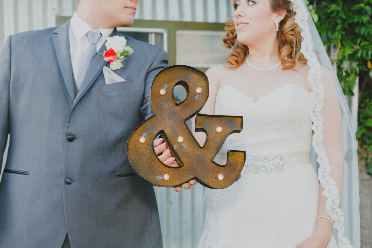 Creative photo of bride and groom holding wedding sign in Oregon