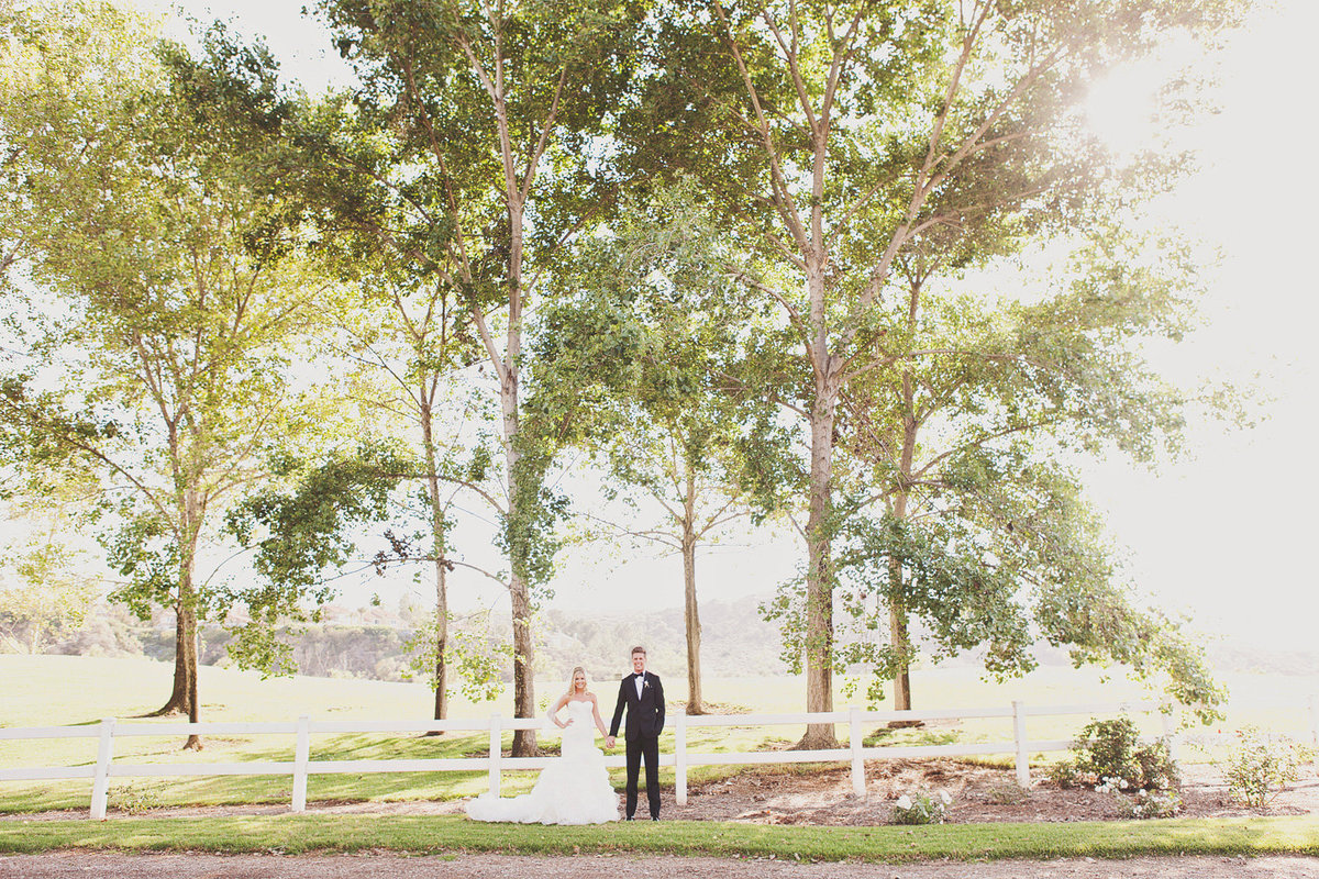 bride and groom holding hands by white fence at Strawberry Farms