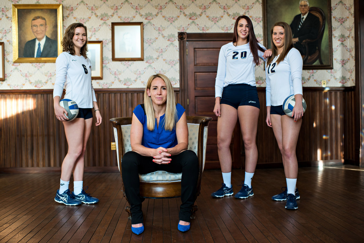 A volley ball coach poses with some of her team members.